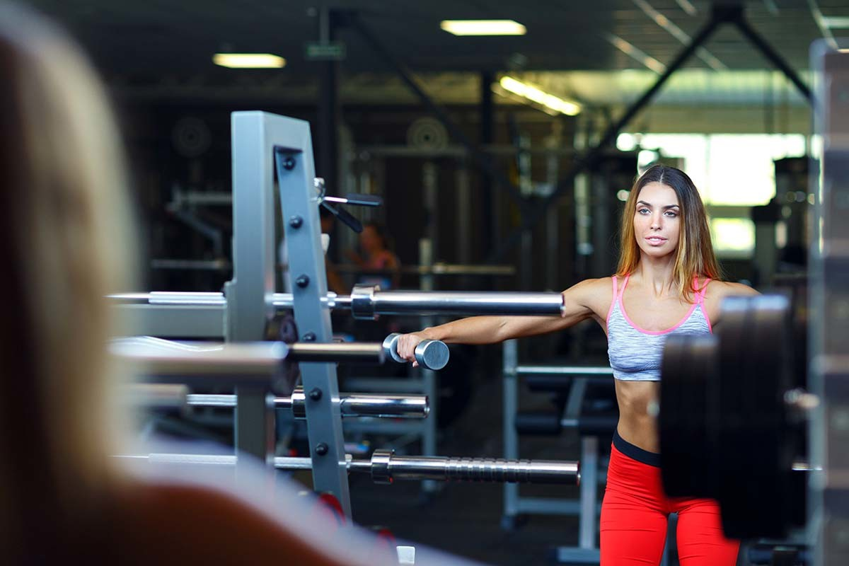 woman with dumbbell in the gym doing exercises